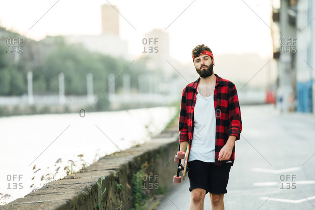 Full body of male skater in plaid shirt and bandana standing with longboard on empty road and looking away