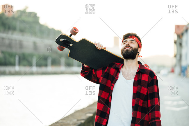 Cheerful bearded male hipster in bandana and checkered shirt standing on promenade with longboard and smiling