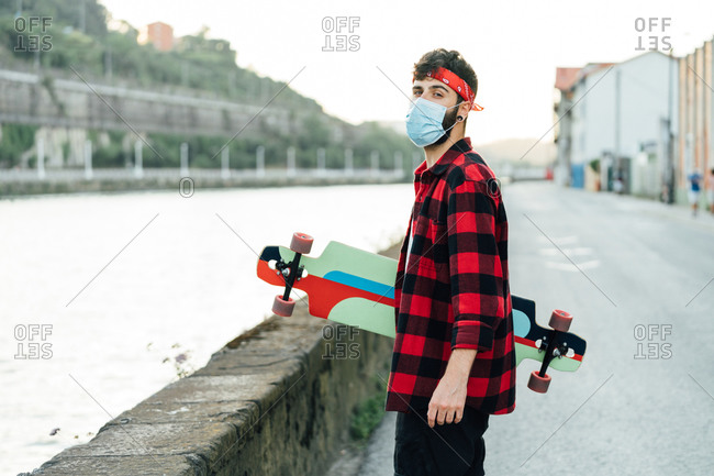 Young male skater in surgical mask and with longboard walking along promenade during coronavirus pandemic and looking at camera