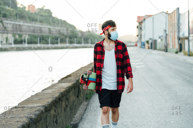Young male skater in surgical mask and with longboard walking along promenade during coronavirus pandemic and looking away