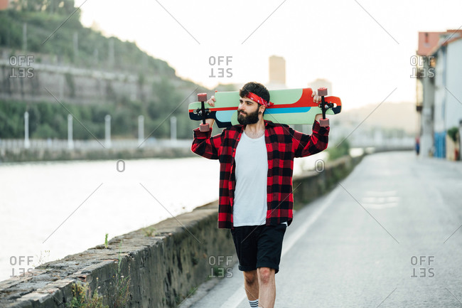 Cheerful bearded male hipster in bandana and checkered shirt standing on promenade with longboard and smiling away