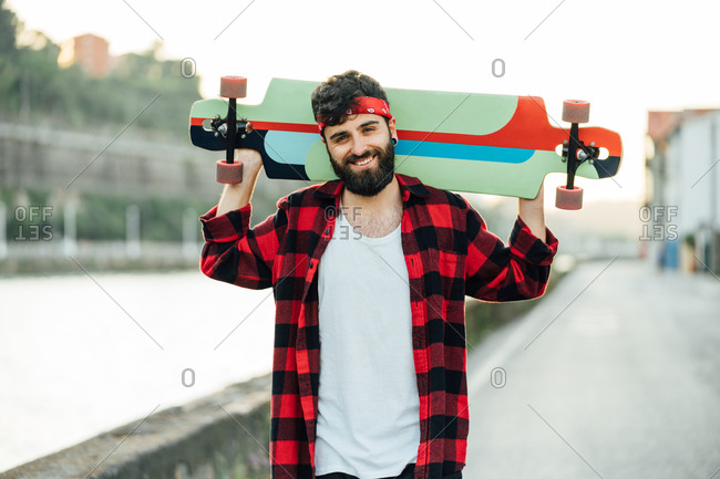 Cheerful bearded male hipster in bandana and checkered shirt standing on promenade with longboard and smiling at camera