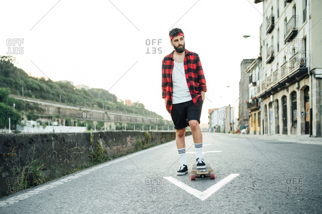 Full body of male skater in plaid shirt and bandana standing on longboard on empty road and looking away