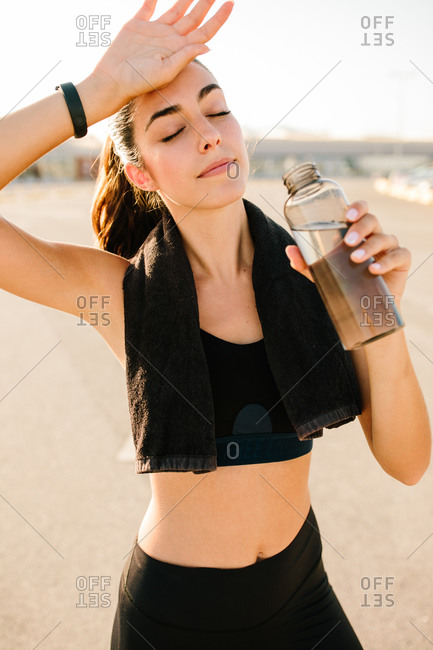 Positive young slim female in sportswear wiping head with hand and drinking fresh beverage from plastic bottle while relaxing after hard training on street
