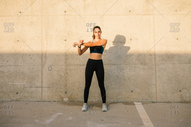 Full body of active young fit female in black sports top and leggings stretching arms while standing against concrete wall in sunny day