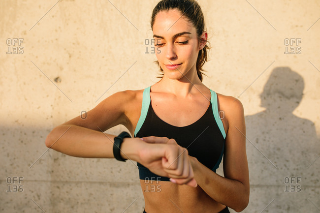 Active young fit female in black sports top and leggings checking sports results on activity tracker while resting standing against concrete wall in sunny day