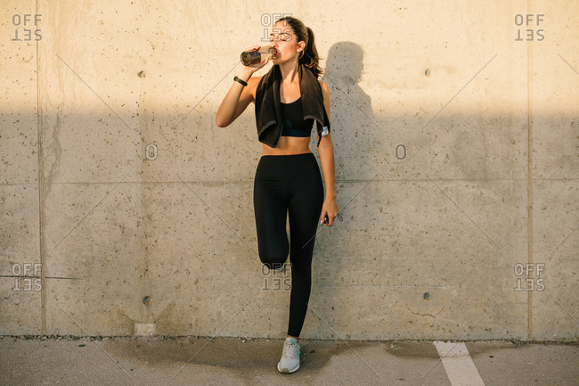Full body young slim female jogger in black sportswear with towel on neck leaning against concrete wall and drinking nutritive beverage after training on street