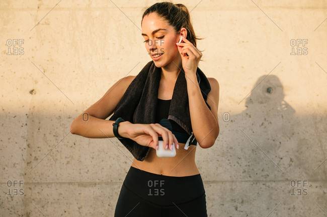 Young slim female in sportswear with towel on neck adjusting earphones and checking results on activity tracker while resting after running against concrete wall