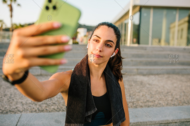 Young slim female in sportswear with earbuds and fitness tracker taking selfie on mobile phone while standing on street after training