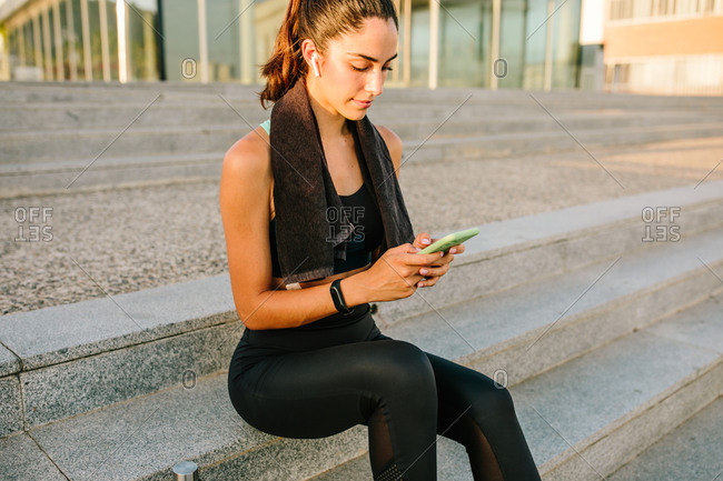 Young slim female in sportswear with earbuds and fitness tracker using mobile phone while standing on street after training