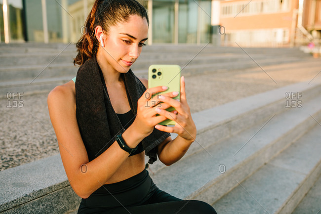 Young slim female in sportswear with earbuds and fitness tracker taking photo on mobile phone while sitting on stairs in the street after training