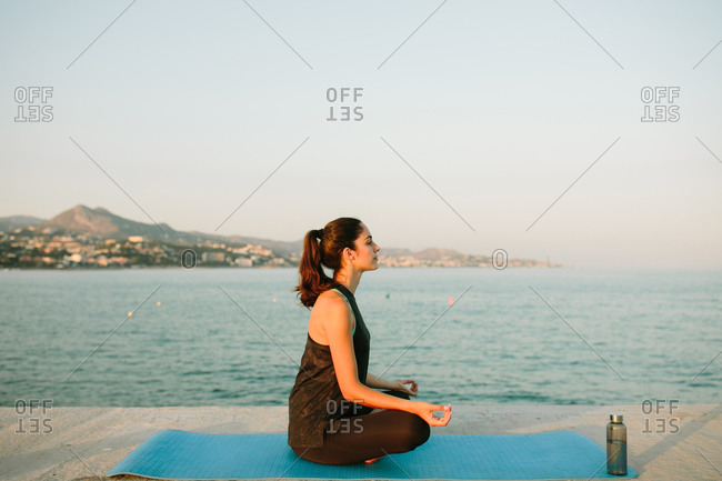 Side view of relaxed female sitting on yoga mat in Padmasana with mudra hands and practicing mindfulness looking away on background of seascape at sunset