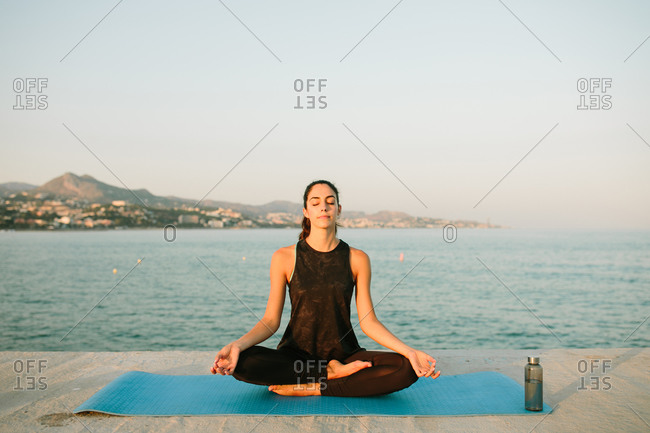 Relaxed female sitting on yoga mat in Padmasana with mudra hands and practicing mindfulness with closed eyes on background of seascape at sunset