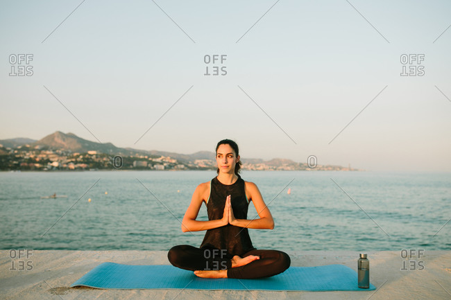 Relaxed female sitting on yoga mat in Padmasana with mudra hands and practicing mindfulness looking away on background of seascape at sunset