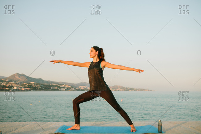 Side view of tranquil female in sportswear standing barefoot on mat and doing yoga in Virabhadrasana on background of amazing seascape during sundown