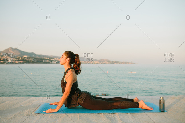 Side view of flexible female in activewear practicing yoga on mat in Bhujangasana near sea during sunset
