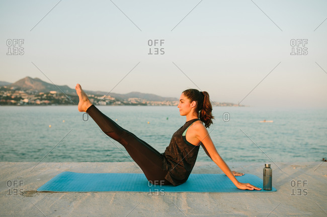 Side view of peaceful female in sportswear sitting on mat in Navasana on pier near sea and looking away