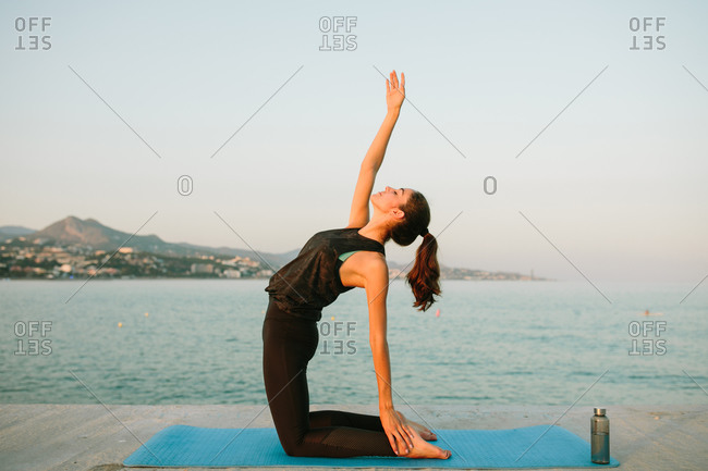 Side view of tranquil female in Ustrasana practicing yoga with closed eyes and raised arm on pier near sea during sundown in summer