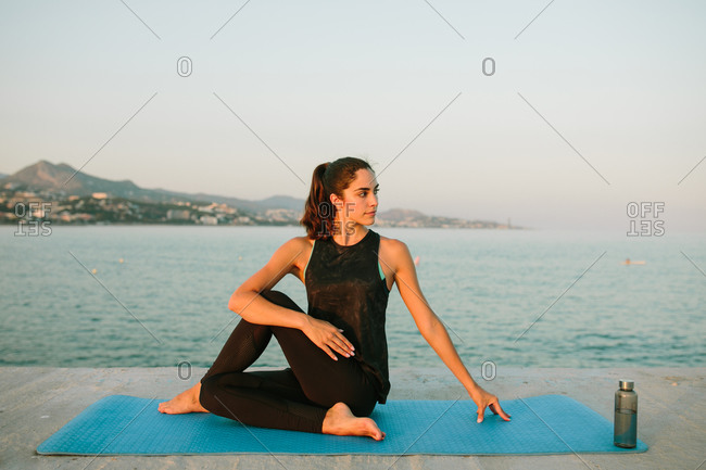 Young carefree female sitting on yoga mat in Ardha Matsyendrasana and stretching body while looking away on background of seascape in evening