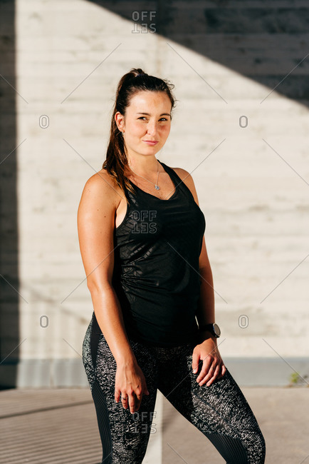 Muscular female athlete in activewear standing resting after workout on sunny day and looking at camera