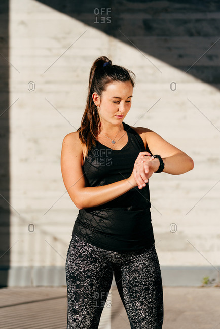 Fit female athlete in sportswear standing in city and checking pulse on fitness tracker during training in summer