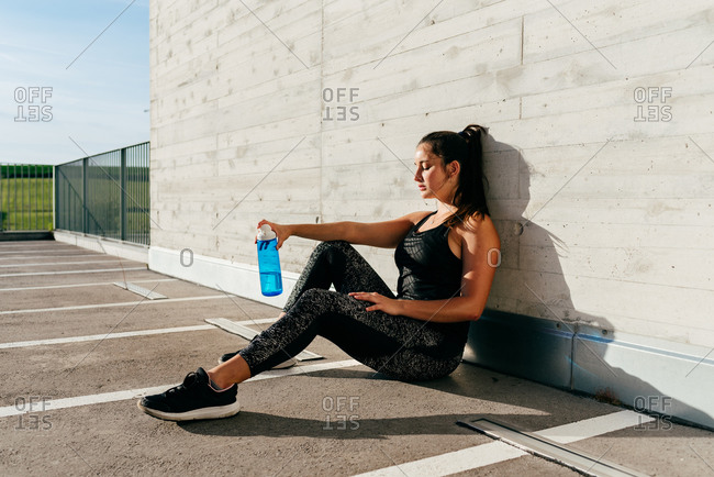 Side view of female athlete in sportswear sitting with bottle of water and relaxing after training on sunny day in summer