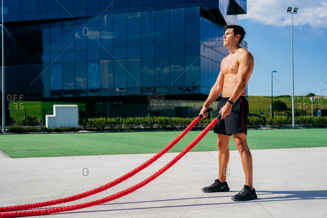 Side view of muscular male athlete with naked torso doing exercises with battle ropes on terrace during sunny day in summer