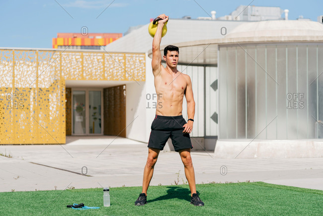 Muscular shirtless sportsman standing on lawn and exercising with heavy kettlebell while looking away