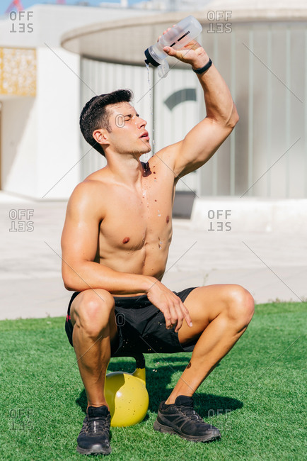 Tired sweaty male athlete with naked torso sitting on kettlebell and pouring water on face with closed eyes after active workout