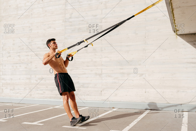 Side view of strong sportsman with naked torso doing exercises with ropes during workout in city on sunny day