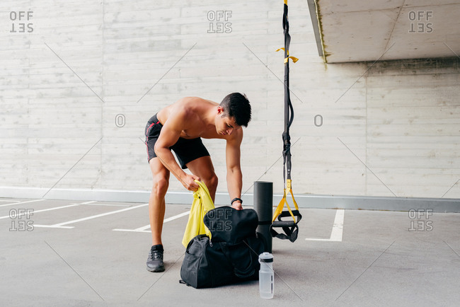 Focused male athlete with naked torso standing near sports bag and preparing for training on street