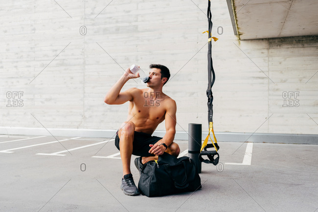 Relaxed sportsman with naked muscular torso crouching on street and drinking clean water from bottle after workout in city