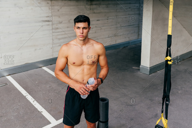 Relaxed sportsman with naked muscular torso standing on street holding water bottle resting after workout in city