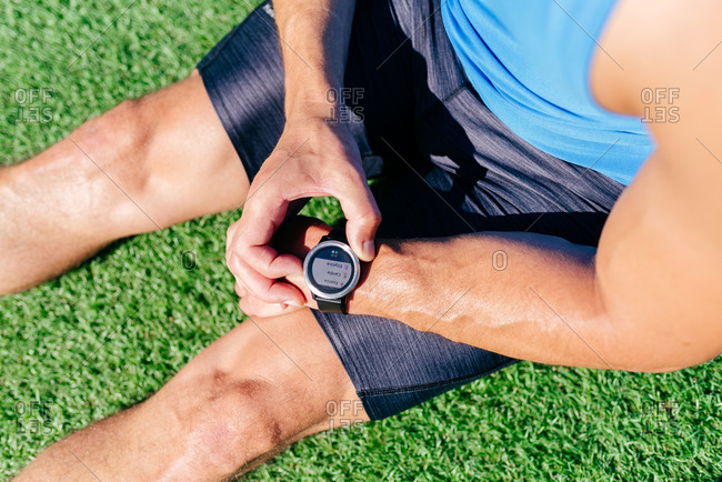 From above of crop unrecognizable muscular male athlete sitting on green lawn and checking fitness smart watch while resting after hard workout outdoors