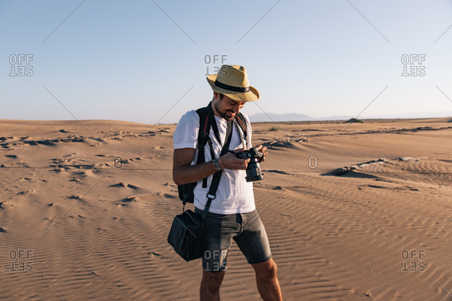 Content man in straw hat carrying photography equipment while using photo camera in hot sandy terrain