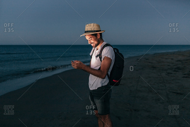 Full body man with backpack standing on sandy coast in light of mobile phone while using in evening
