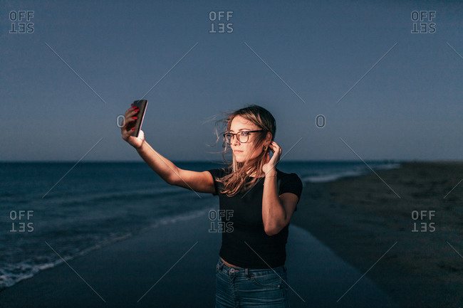 Calm female in glasses using mobile phone with flashlight while taking selfie on coastline at night