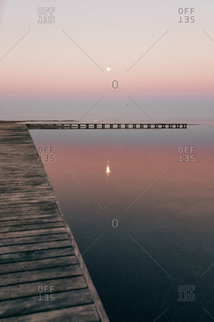 Perspective wooden walkway on calm water of Ebro river against sunset sky in mist