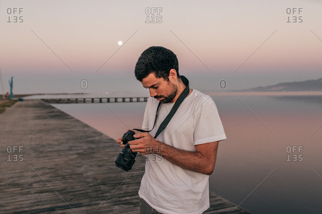 Focused man using modern photo camera standing on paved wooden pier of Ebro Delta river in sundown