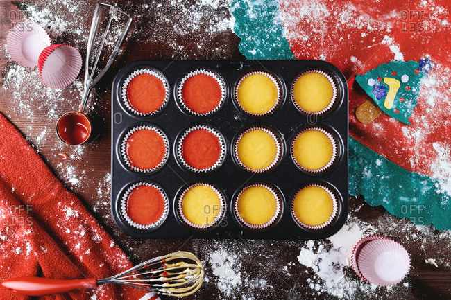 Top view of metal baking dish with paper cupcake cups filled with colorful dough during pastry preparation for Christmas holiday