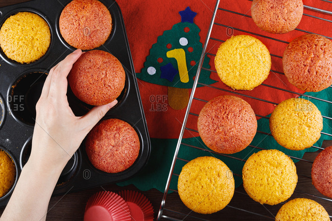 Top view of crop anonymous female putting freshly baked colorful cupcakes from baking pan on metal grid while preparing pastry for Christmas party