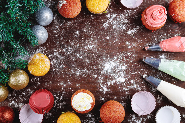 Top view composition with colorful cupcakes and confectionery utensils arranged with green spruce branches on table sprinkled with white sugar powder