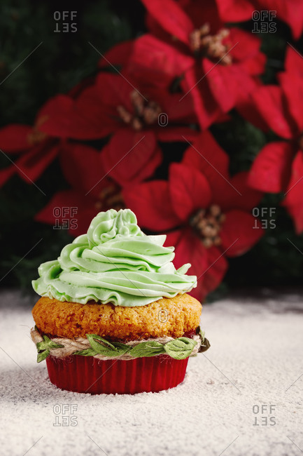 Yummy colorful cupcake with whipped cream in red paper cups decorated with green rope placed near Christmas tree branches on table sprinkled with sugar powder