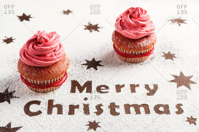 From above of delicious sweet cupcakes with pink frosting arranged on table sprinkled with sugar powder and decorated with stars and Merry Christmas text