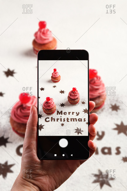From above of crop anonymous person with smartphone taking picture of colorful cupcakes with frosting and cherry berries arranged on table with Christmas decoration