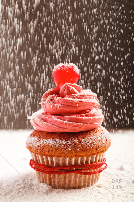 Closeup of delicious sweet cupcake with pink frosting and red cherry sprinkled with white sugar powder served for Christmas celebration