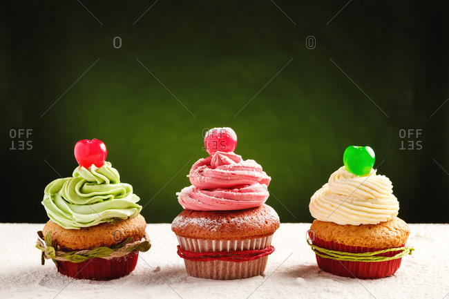 Yummy festive Christmas cupcakes decorated with colorful frosting and cherry berries placed on table sprinkled with white sugar powder against green background