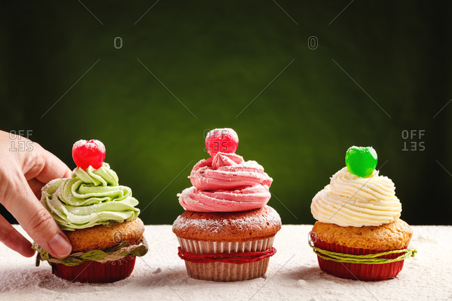 Crop anonymous person taking delicious homemade festive cupcake with green colored whipped cream from table