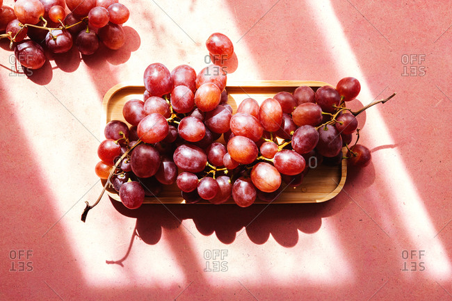 Top view of bunch of delicious fresh juicy red grapes served on wooden tray on pink background with sunlight and shadows