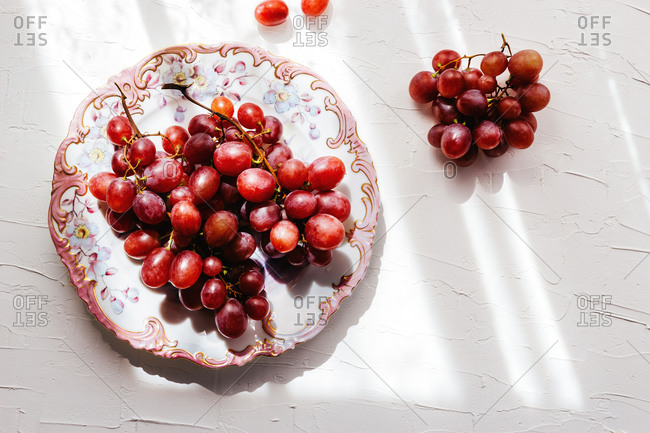 Top view of ornamental plate with ripe red grapes placed near bunch of grape on white table